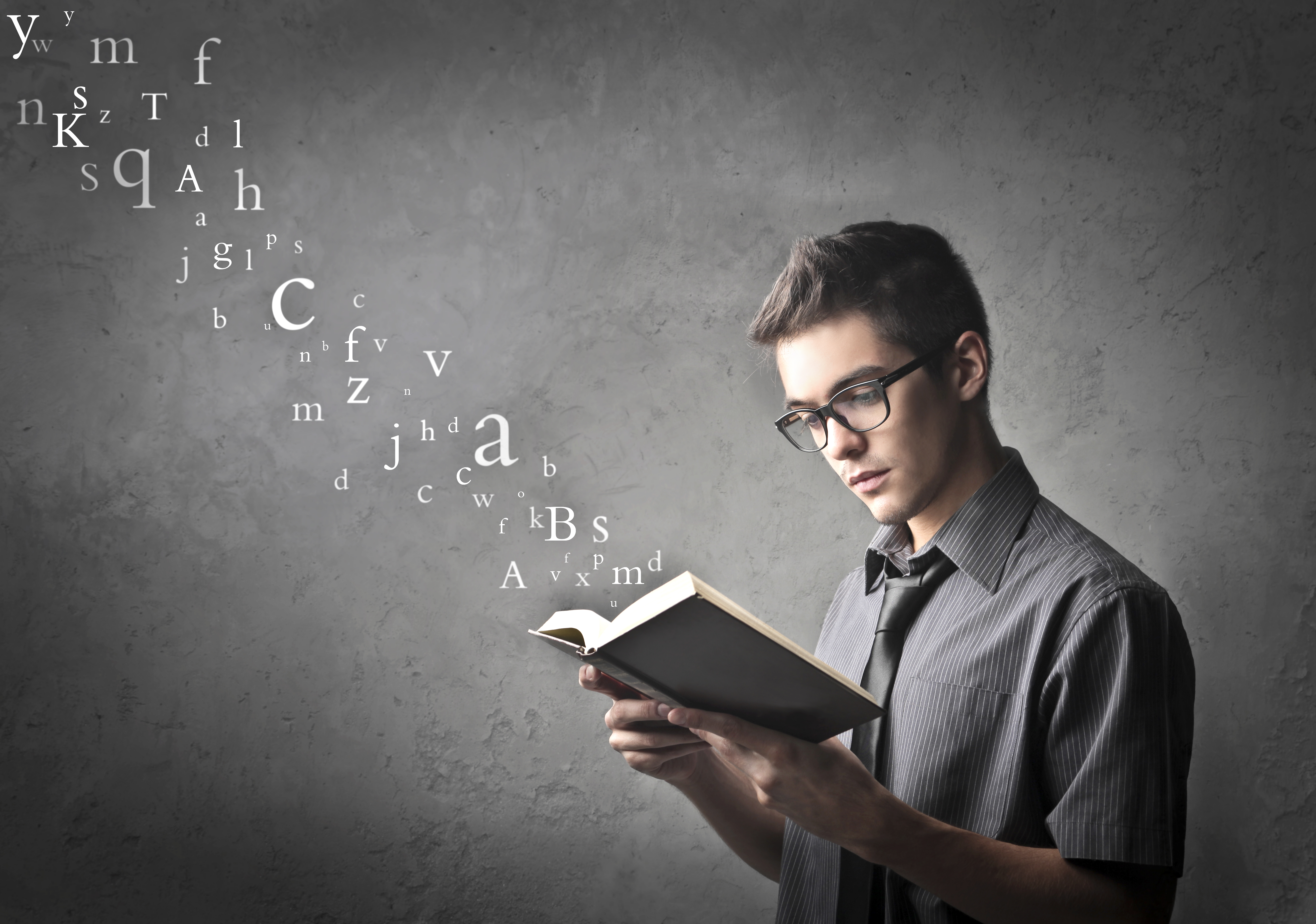 A standing teenage boy reading a book in front of a grey background with a stream of letters floating up to the sky
