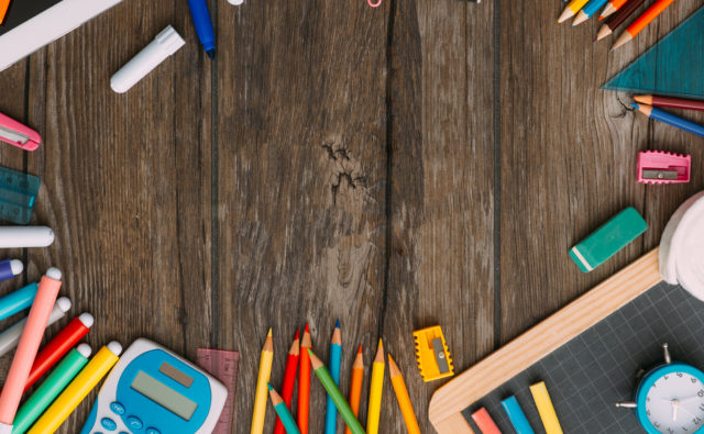 School and education banner with colorful pencils and stationery, back to school text at center, flat lay